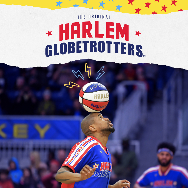 Harlem Globetrotter balancing basketball on head while crowd watches