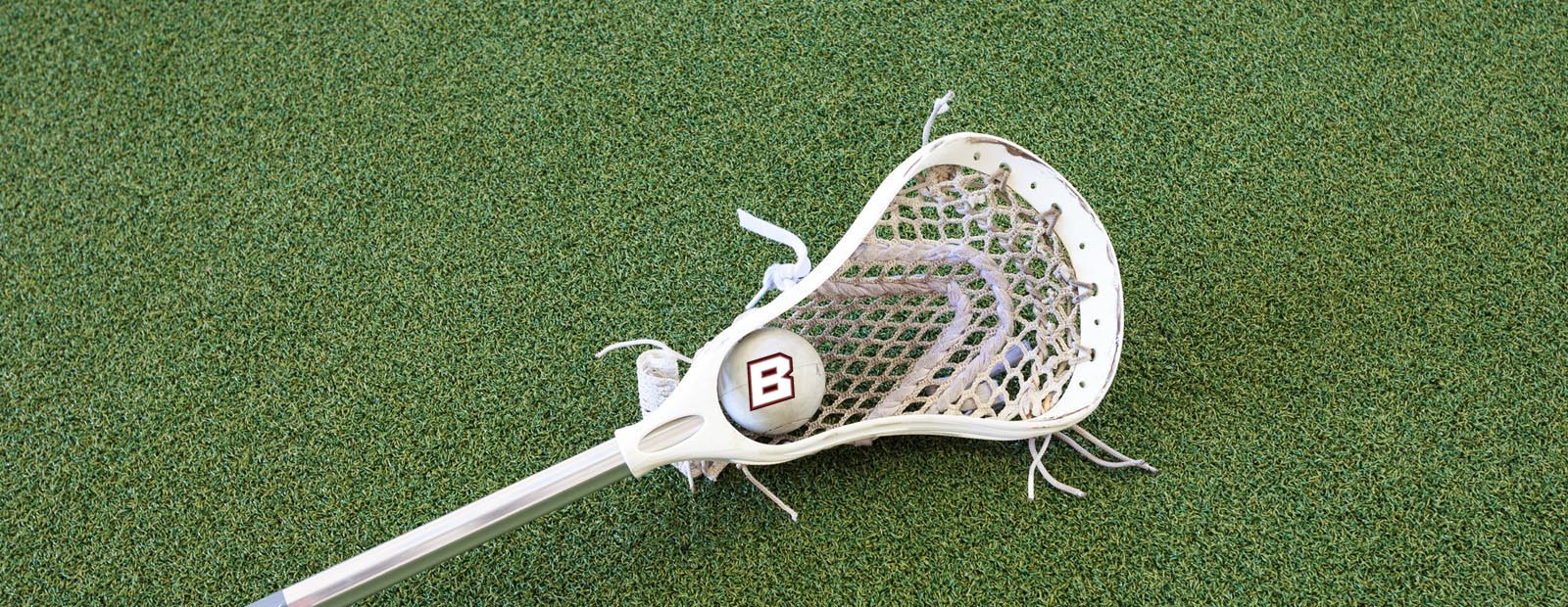 Lacrosse stick with ball laying on grass