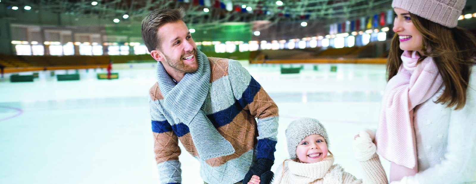 Husband and wife skating in arena with daughter